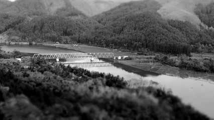 TIlt shift view of train bridge across serayu river in Indonesia in black and white