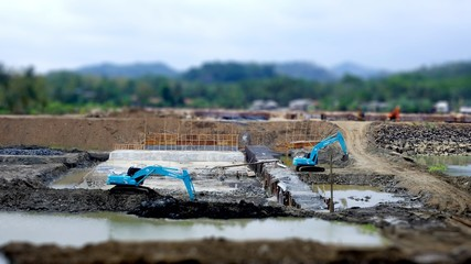 Tilt shift photo about blue excavator working in construction site