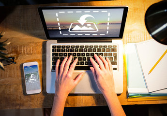 User with Laptop and Smartphone on Rustic Desk Mockup