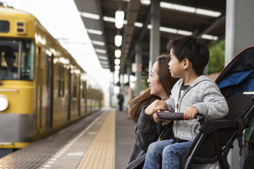 Parents and children are waiting for a train on the platform