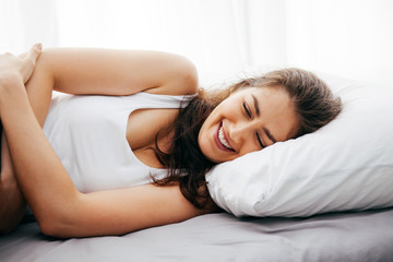 Young beautiful Caucasian woman lying on bed being happy and smiling