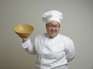 Asian lady fat chef with bowl in hand on plain background with happy face
