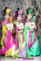 Three women in old traditional chinese dresses with fans