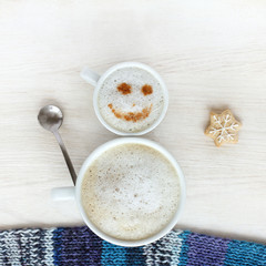 good mood for winter coffee break/ small and large cup of frothy cappuccino standing together in a cheerful snowman top view