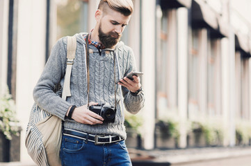 Outdoor portrait of modern young tourist man using mobile phone in the street
