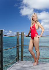Young pretty woman stands in bathing suit on platform at villa on water
