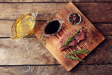 Raw steak with herb and spices on wooden cutting board