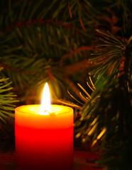 Christmas burning candle with New Yera`s tree brunch on dark background