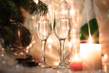 New Years Eve celebration background with an elegant arrangement with a clock counting down to midnight, flutes and bottle of champage and party garland with a cracker, bubble bokeh