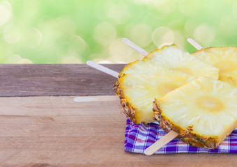 Pineapple with Ice cream stick on wooden table.