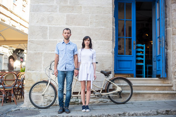 Man and woman stand holding hands and looking at camera on the background of their tandem bicycle, walls and vintage door on the sidewalk of a city street