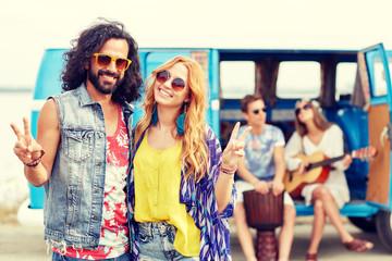 hippie friends over minivan car showing peace sign