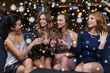 happy women with champagne glasses at night club