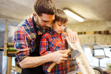 father and son with ax and wood plank at workshop
