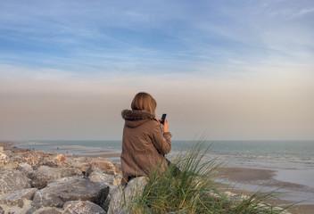 femme et son portable le soir sur la côte