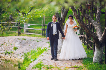 Groom and Bride in a park. wedding dress. Bridal wedding bouquet of flowers. Newlyweds on nature.