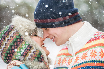 Happy couple in love in the park. Man and woman dressed in a sweater and warm hats, mittens. Snowfall. Trees in the snow, winter forest. Emotional people. Bright multi-colored sweater.