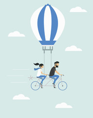 Young couple on the air balloon riding bicycle. Flying on the sky