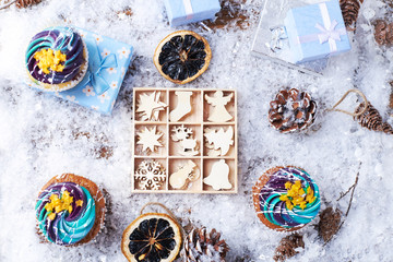 Winter cupcakes with gradient cream and golden stars on a snow with presents, wooden toys, cone and snowflakes on a background. Winter mood. Top view