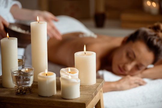 Young beautiful girl relaxing in spa salon. Focus on candles.
