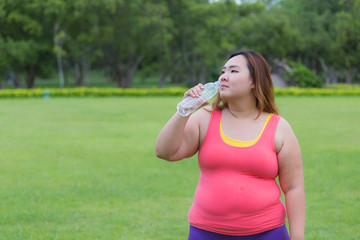 Beautiful fat woman drinking water after finish her workout.