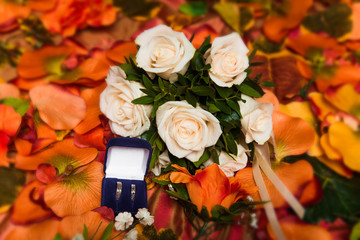 wedding bouquet of white roses and two wedding rings in blue box