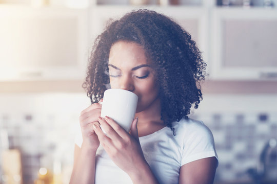 Pleasant young woman drinking coffee