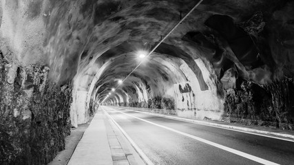 Тunnel in the mountain with a footpath, stretching into the distance. Diminishing perspective. Interesting structure of the stone. Black and White.