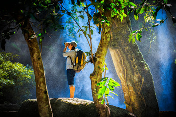 traveler use binoculars in water fall, water spray spreading aro