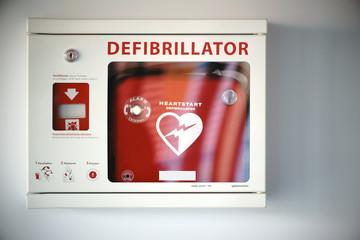Defibrillator / Ein Überlebenskasten mit einem Defibrillator an einer Wand eines öffentlichen Gebäudes.