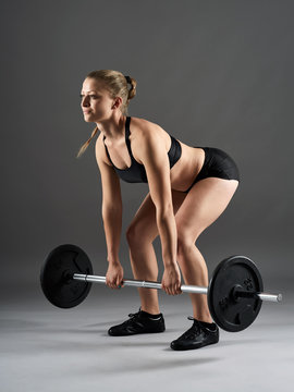 Fitness girl with barbell doing deadlift