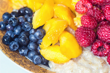 Organic oatmeal porridge in white ceramic bowl with raspberries, peaches and blueberries. Healthy breakfast - health and diet concept on the wooden table, close up.