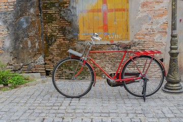 Vintage Red bicycle near the window of old brick wall home