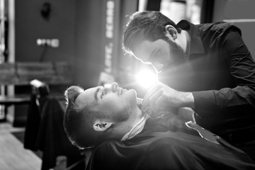 The Barber man in the process of cutting the beard of a client in a Barbershop, black and white photo