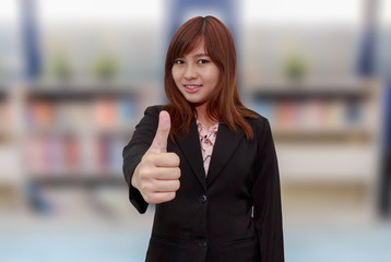 Smiling businesswoman holding thumps up in font of book shelf