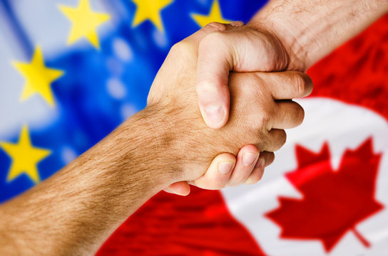 Hands shaking over Canadian and European flags symbolizing trade deal