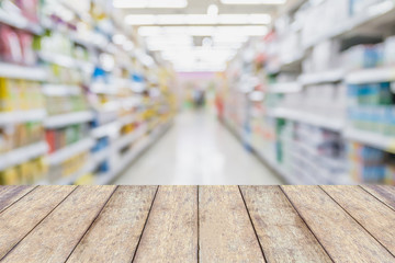 Wooden table top with blur supermarket aisle background
