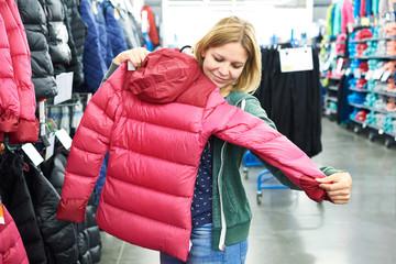 Woman chooses winter jacket in store