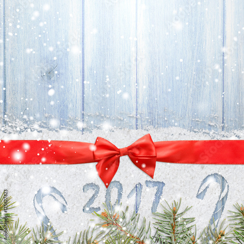 christmas card or new year background made of red satin ribbon with bow on snow and
