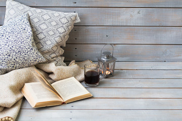 Cushions, plaid, lantern, black coffee and old book on the white