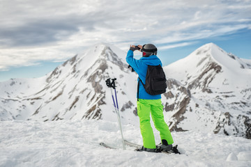 Skier making photo of a beautiful landscape high in mountains.