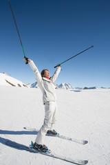 femme souriante les bras en l'air sur des skis à la montagne