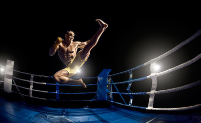 Thai boxer on boxing ring, jump and kicking