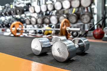 iron dumbbells in gym , interior indoor