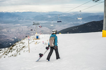 Man with a snowboard in his left hand, walking toward a ski lift.