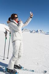 femme souriante qui se prend en photo avec son téléphone sur une piste de ski