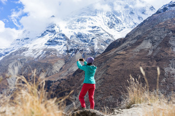 Hiker taking picture of beautiful  mountains snowy peaks on smartphone. Travel concept. Himalayas, Nepal