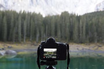 Panorama del Lago di Carezza,Italia, con una macchina fotografica in primo piano