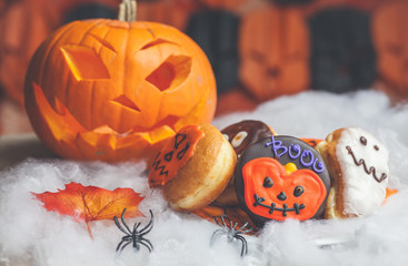 Halloween pumpkin, plastic spider and festive cakes