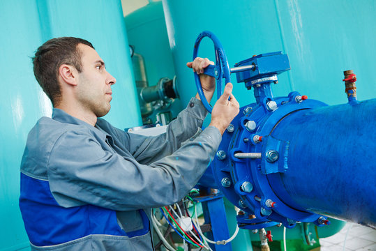 serviceman operating industrial water purification or filtration equipment